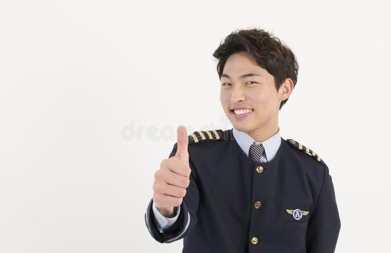 Uniforme d'uso pilota di linea aerea allegra con il pollice sul gesto di approvazione immagine stock