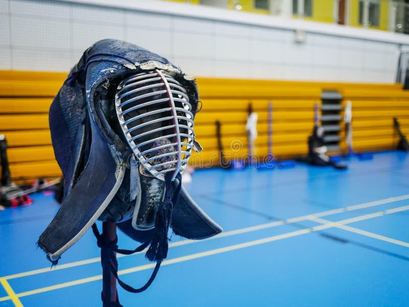 Uniforme da máscara do capacete de Kendo com espaço da cópia | O estudante aprende jogar a espada de madeira imagem de stock