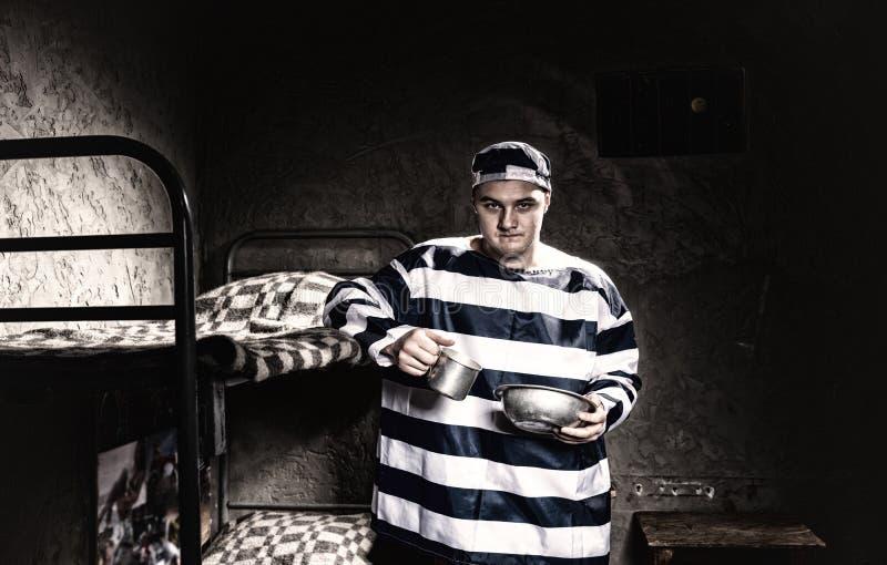 Uniforme de la prisión del preso que lleva enojado que sostiene los platos de aluminio adentro foto de archivo