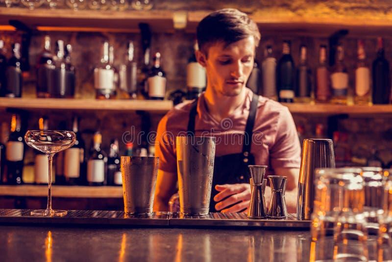 Uniforme de port de barman aux cheveux foncés occupé faisant le cocktail image libre de droits