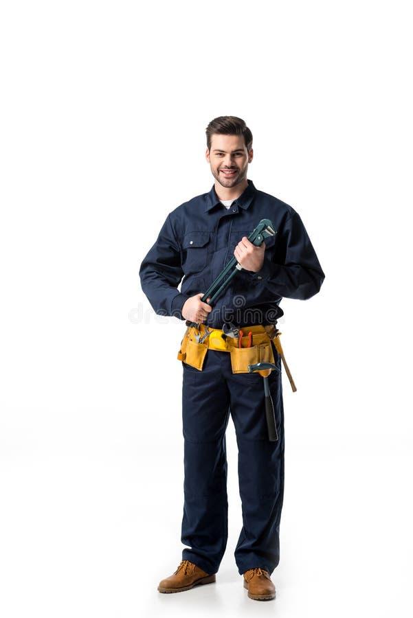 Uniforme de port de bricoleur sûr avec la ceinture d'outil et la clé de se tenir photographie stock libre de droits