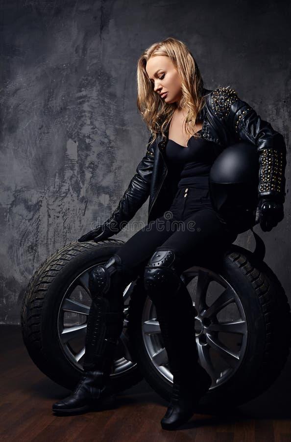 Uniforme del corredor de la mujer que lleva hermosa, presentando en un estudio mientras que se sienta en una rueda y sostiene un  fotos de archivo