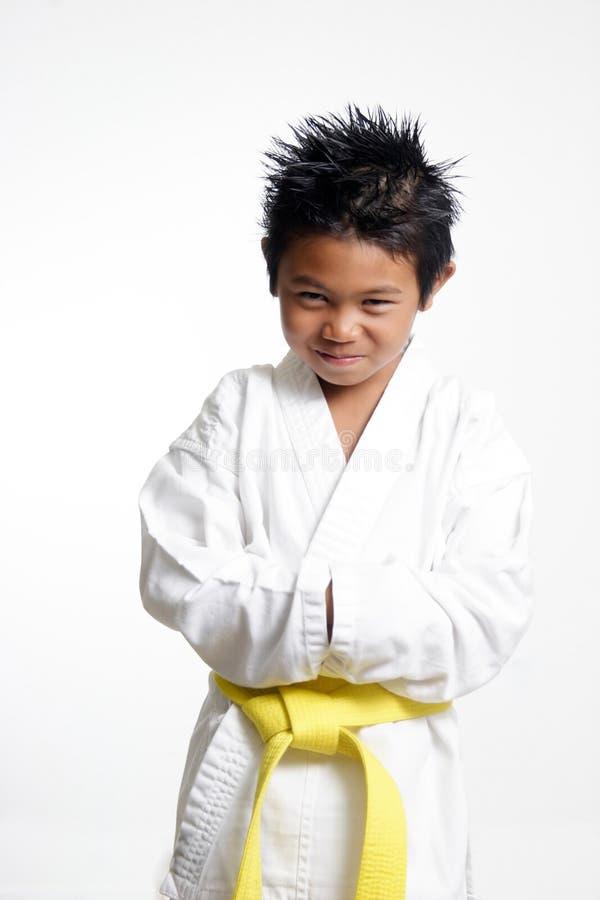 Uniforme del karate del cabrito que desgasta foto de archivo