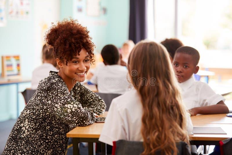 Uniforme elementare di Helping Pupils Wearing del maestro di scuola come funzionano allo scrittorio in aula fotografia stock