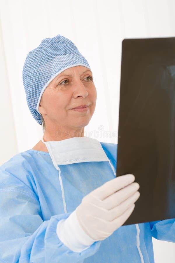 Uniforme fêmea do raio X da preensão do cirurgião sênior imagem de stock royalty free