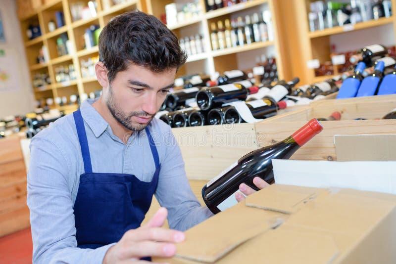 Uniforme que lleva del vendedor alegre del hombre joven en casa del vino fotografía de archivo libre de regalías