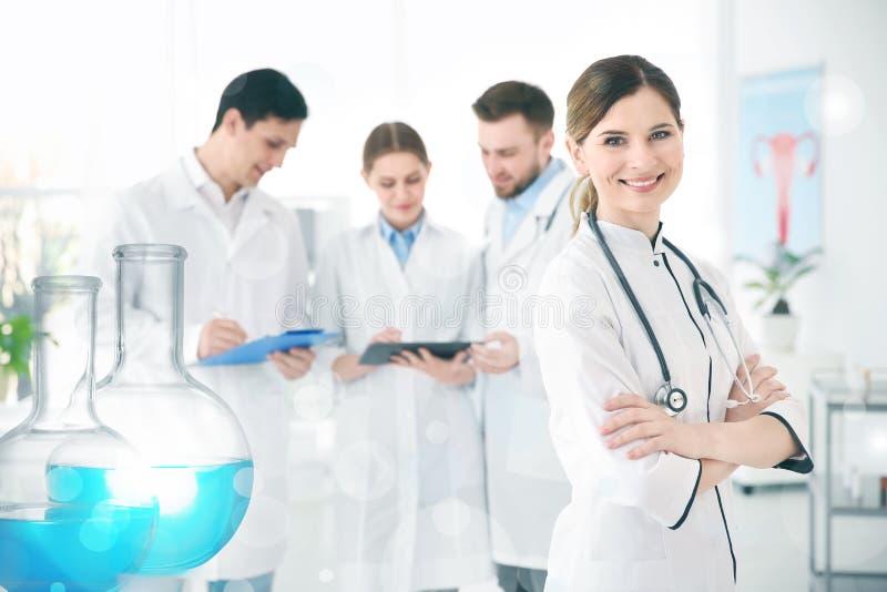 Uniforme que lleva sonriente del doctor de sexo femenino en hospital moderno fotografía de archivo