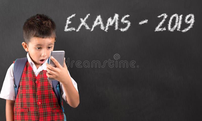 Uniforme scolaire de port de garçon regardant le téléphone portable avec l'expression choquée sur son visage image stock