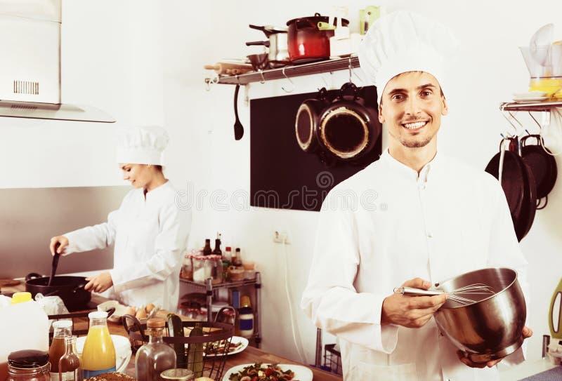 Uniforme vestindo do cozinheiro dos jovens que trabalha na cozinha fotografia de stock royalty free