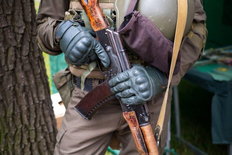 Uniforme vestindo do soldado com a metralhadora nas mãos no luvas táticas Imagem com conceito militar Avtomat Kalashnikova fotografia de stock royalty free