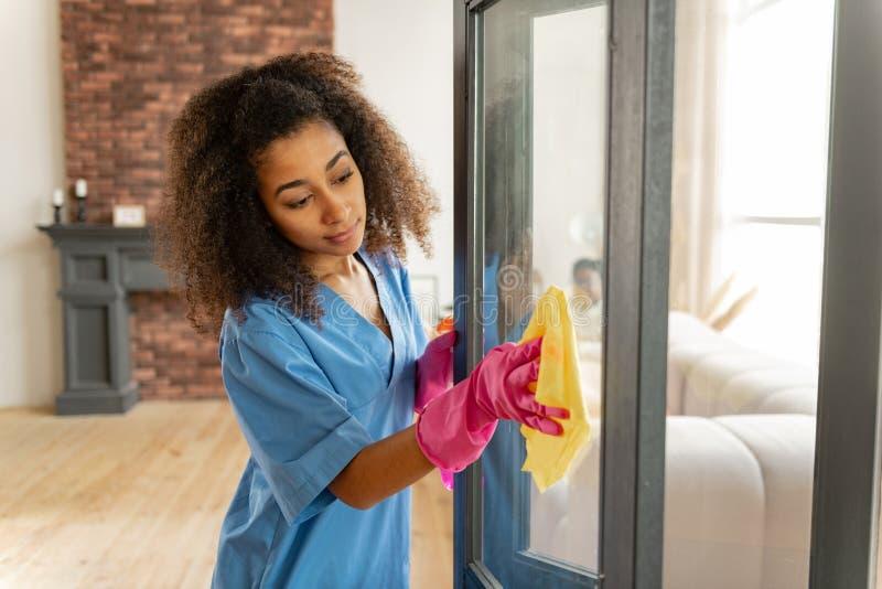 Uniforme vestindo e luvas do assistente médico que limpam a porta de vidro imagens de stock