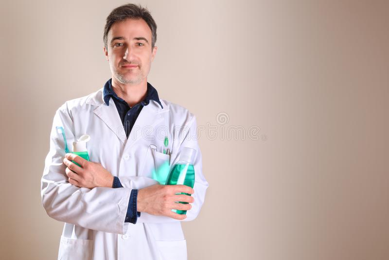 Uniformed dentist with dental tools with crossed hands royalty free stock photo