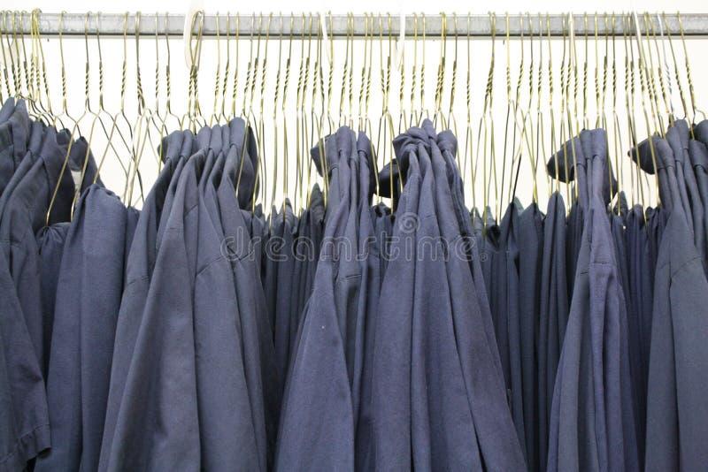 Uniformes das camisas do trabalho de colarinho azul em ganchos fotos de stock royalty free