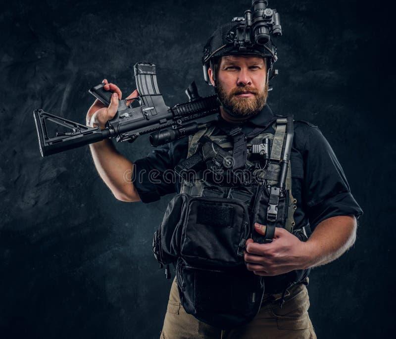 Uniformes de un combate del soldado valiente de las fuerzas que llevan especiales con los dispositivos modernos que presentan con imagen de archivo libre de regalías
