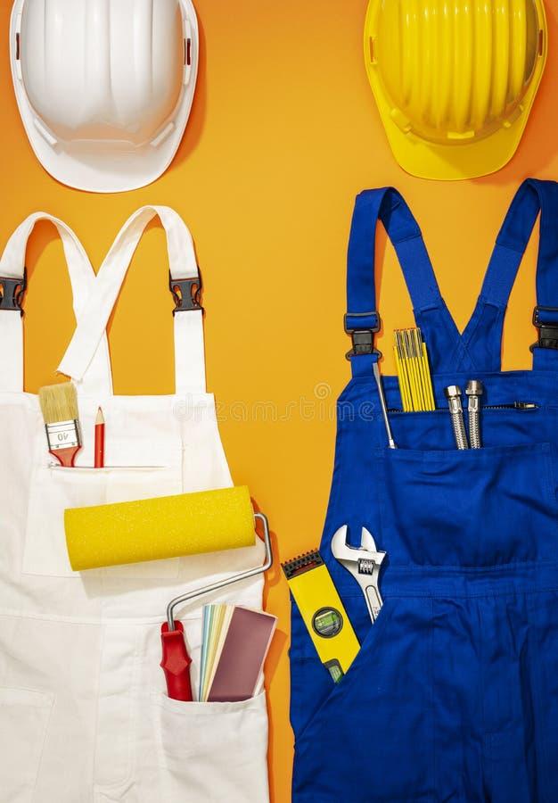 Uniformi del lavoro del pittore e del riparatore con gli strumenti immagini stock libere da diritti