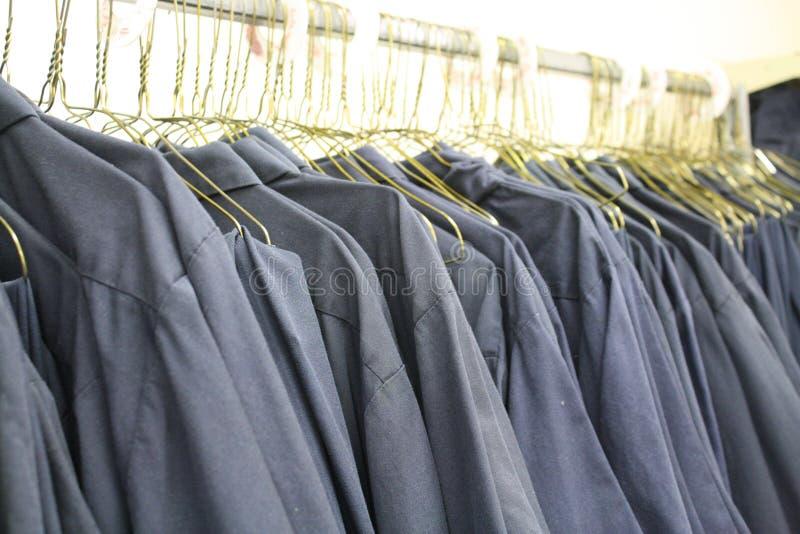 Uniformi delle camice del lavoro di collare blu sui ganci immagini stock