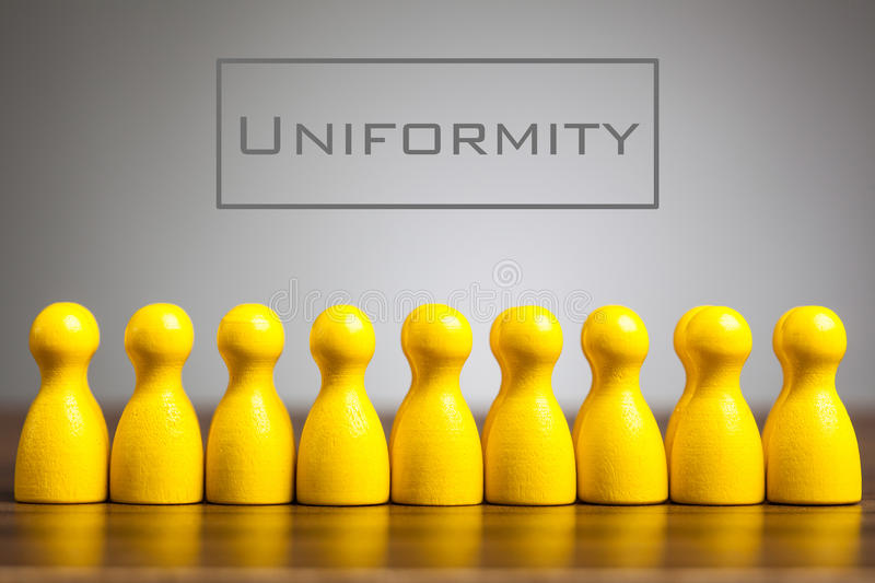 Uniformity concept with pawn figurines on table,. Grey background royalty free stock images
