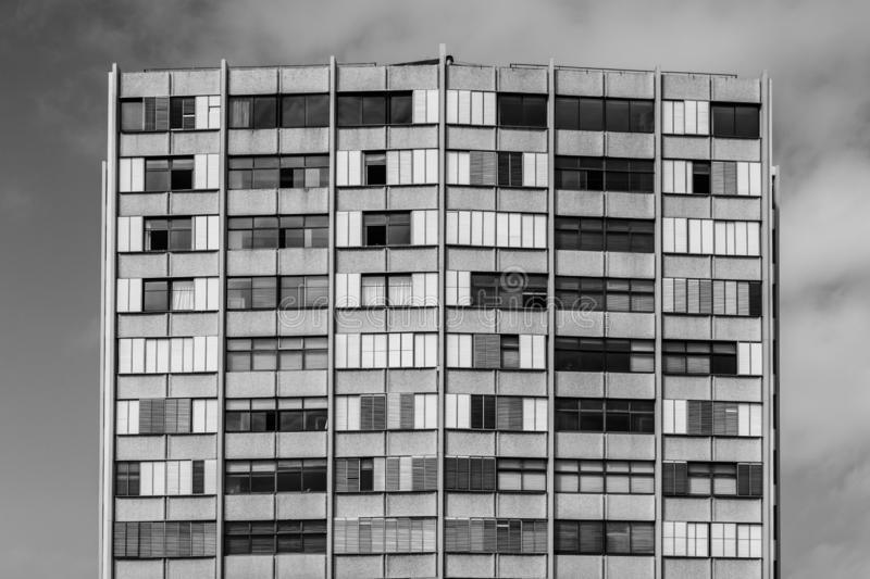 Uniformity and Shuttered Windows in Tall Apartment Block. Vertical and horizontal lines create a sense of chaos and tension in this black and white image of a stock image