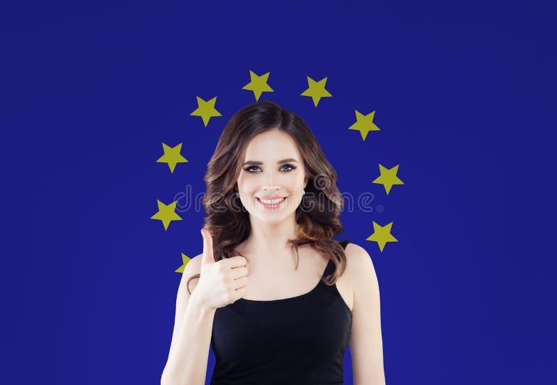 Unii Europejskiej pojęcie z szczęśliwą kobietą pokazuje kciuk w górę UE flagi tła przeciw Podróż i nauka w Europa obrazy stock