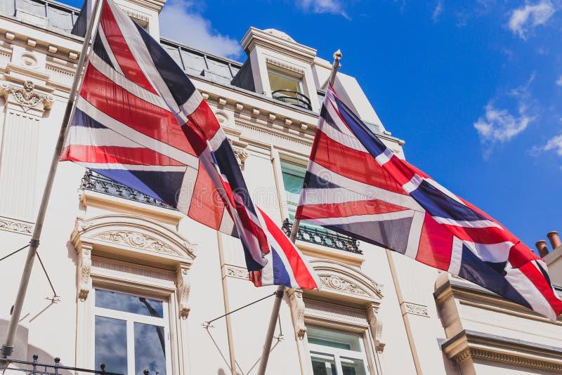 Uniion Джек сигнализирует развевать от шикарных зданий в центе города Лондона стоковое изображение
