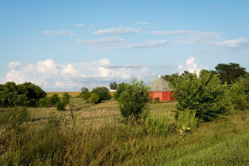 Unik rund röd ladugård som omges av öppen jordbruksmark i lantliga Illinois royaltyfria bilder