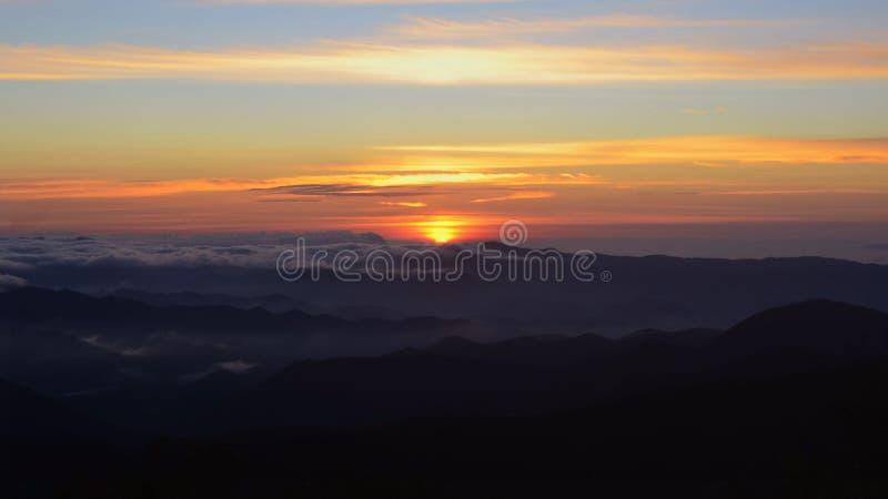 Unik solnedgång i bergen som täckas med moln arkivfoto