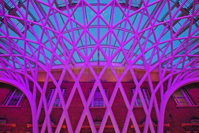 Unik struktur på folkhop av den London konungen Cross Railway Station mot tegelstenbruntbyggnaden royaltyfria foton