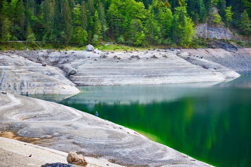 Unikalny surrealistyczny widok Vorderer Gosausee jezioro z Dwa ludźmi na tle Prześwietny widok woda i spokój zdjęcie royalty free