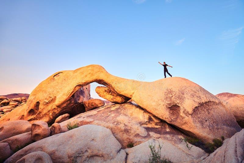 Unikt vagga bildande med den kvinnliga klättraren på solnedgången arkivbilder
