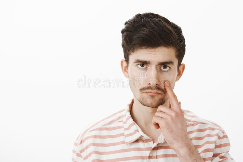 Unimpressed with boring conversation. Displeased bored guy in casual striped shirt, pulling eye and showing eyelid with. Indifferent careless expression stock images