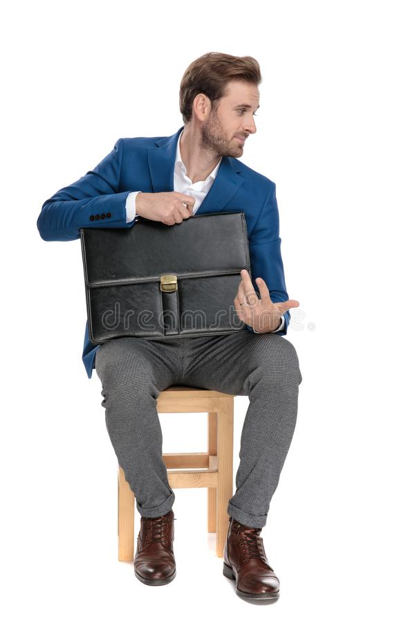 Unimpressed businessman holding his briefcase and disagreeing stock photo