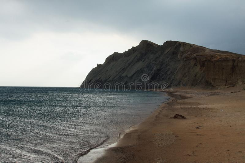 Uninhabited sea shore. A mountain of clay is foreground royalty free stock images