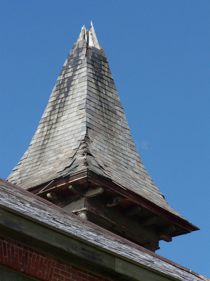 Uninspiring. Old spire on top of a church in great need of repair and renovation stock photos