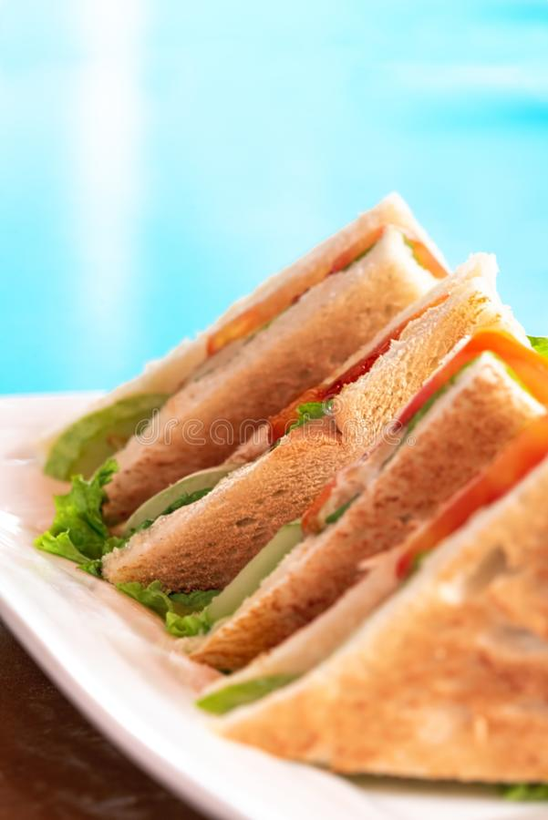 Union Club House Sandwich being serve beside the turquoise blue swimming pool or beach. Selective Focus. Concept of breakfast while vacation royalty free stock image