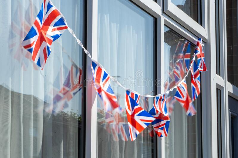 Union jack bunting or british flags on the outside of a British house royalty free stock photography