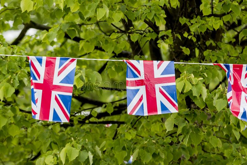 Union Jack bunting flapping in the breeze celebrating British event outside a shopping centre in England, United Kingdom stock photo