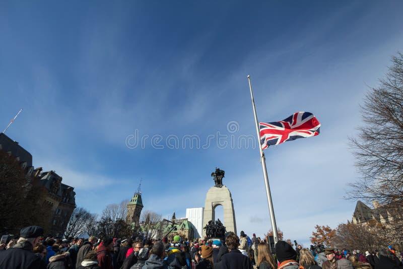 Union Jack flagga framme av en folkmassasammankomst p? den nationella krigminnesm?rken, p? minnedag arkivbild