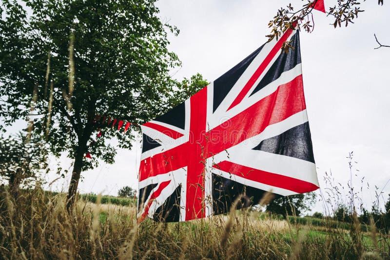 Union Jack-Flagge ausgedehnt zwischen Bäume stockfotos