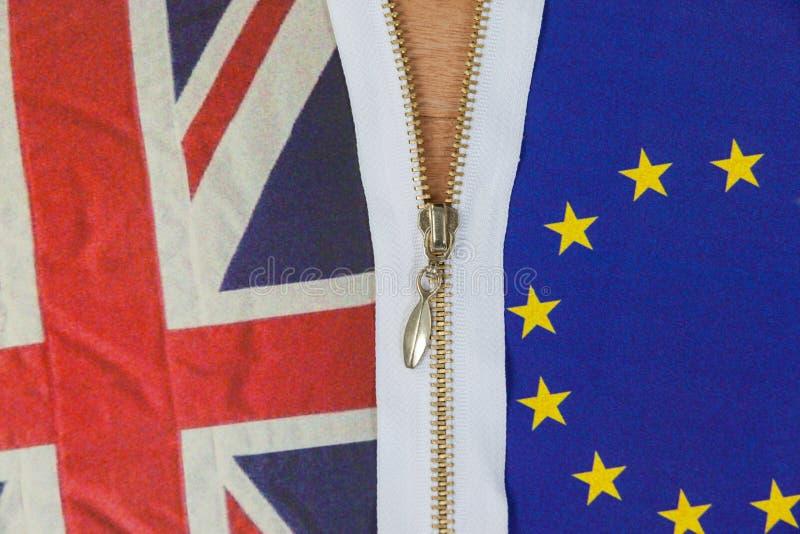 Union Jack och europeisk facklig flagga som dras ned blixtlåset på för att visa brexitfolkomröstningbegrepp royaltyfri fotografi