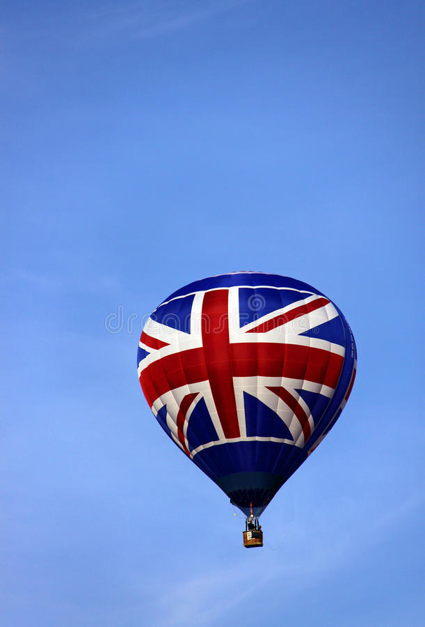 Union Jack UK flag hot air balloons rising. Red white and blue Union Jack UK flag hot air balloon rising in a blue sky stock images
