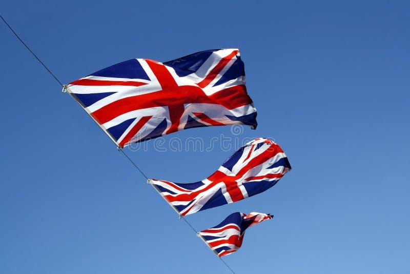 Union jacks. Three union jack flags flying against a deep blue sky royalty free stock photos