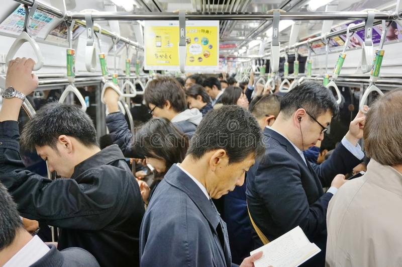 Commuters on a Tokyo metro train royalty free stock photography