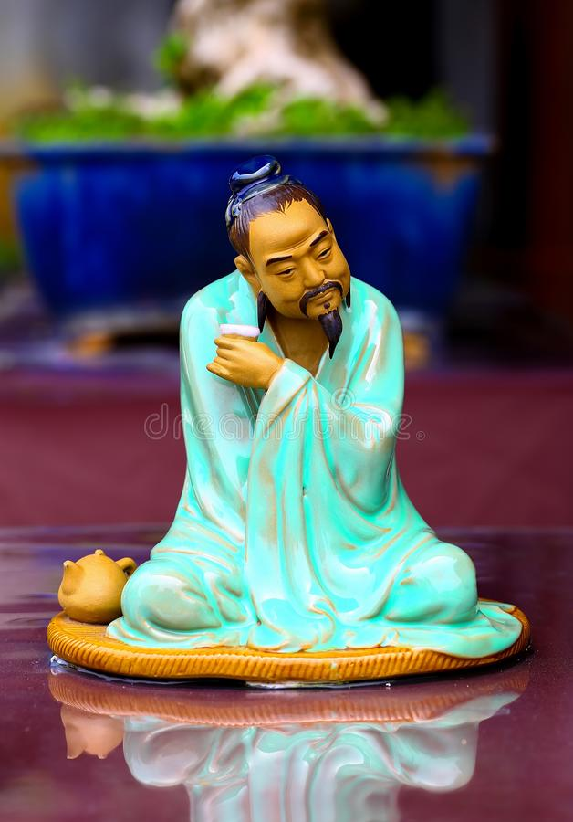 Miniature chinese zen statue with reflection stock photography