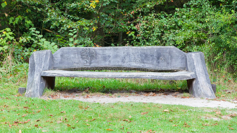 Unique bench in a park. Solid wood with a carving of a tree royalty free stock images