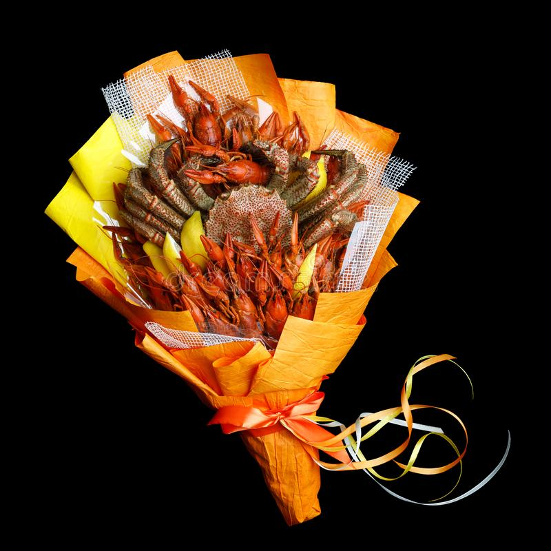 Unique bouquet consisting of large crab and boiled crawfish wrapped in orange paper on a black background.  stock photography