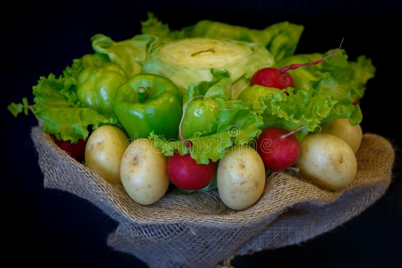 Unique bouquet consisting of paprika, cabbage, radish, potatoes, salad leaves as a gift on the dark background.  stock photography