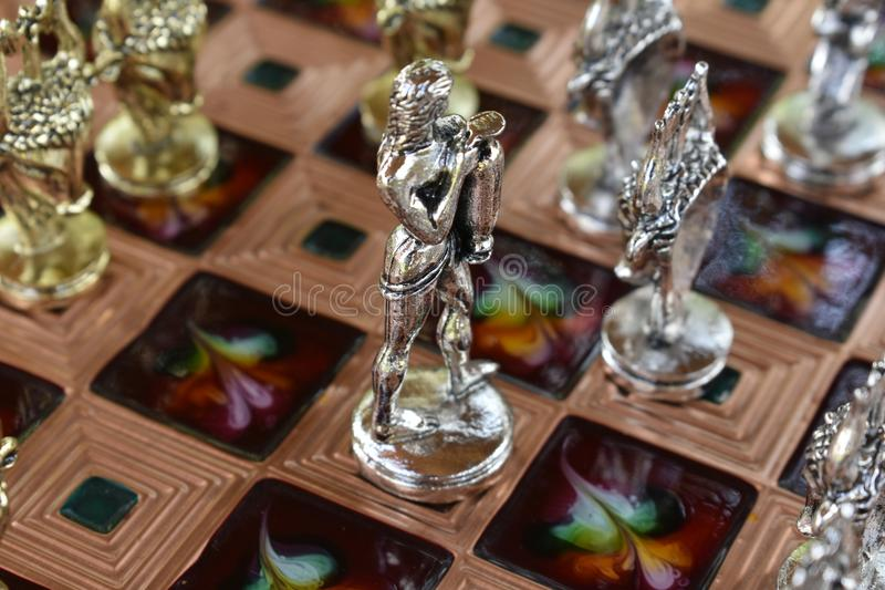 Unique chess Board, unusual chess pieces. Metal sculptures on a wooden Board. The game goes on royalty free stock image