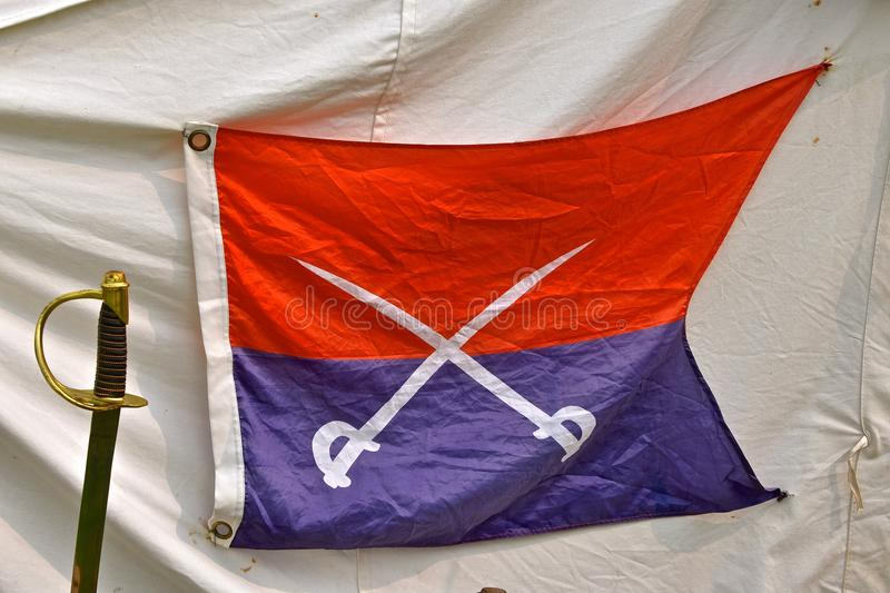 Civil War era flag or banner with bayonets. A unique Civil War era bayonet and flag or banner are displayed on a white canvas officer`s tent at a re-enactment stock images