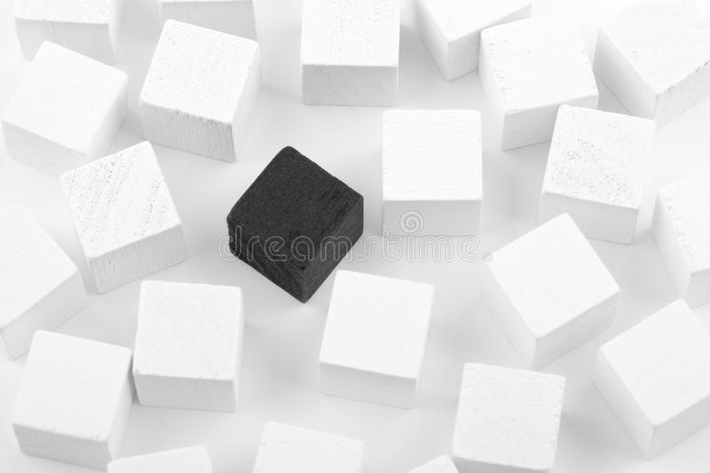 Unique concept. Black cube in a group of white blocks royalty free stock image