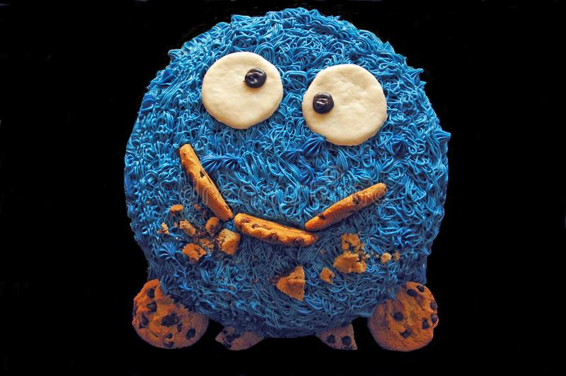 Unique cookie monster cake on a black background stock photography